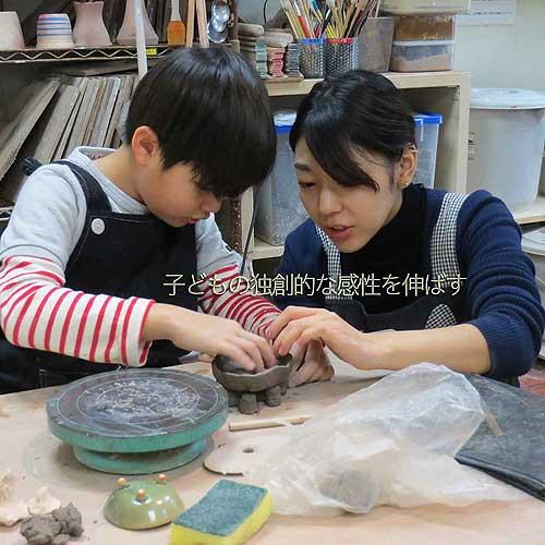先生に陶芸を学んでいる最中の小学生男子
