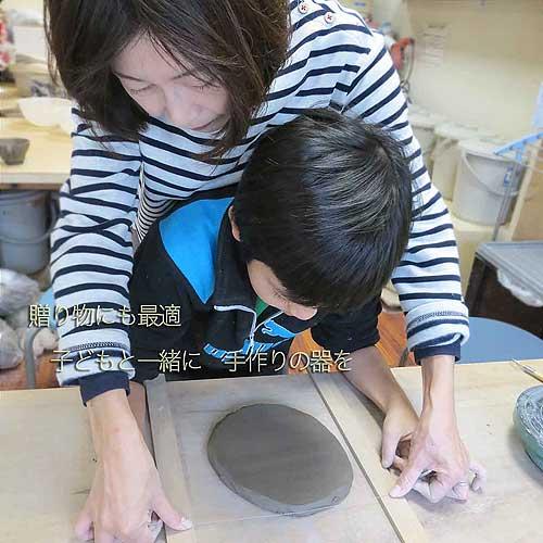 お母さんが息子の陶芸制作を手伝っている