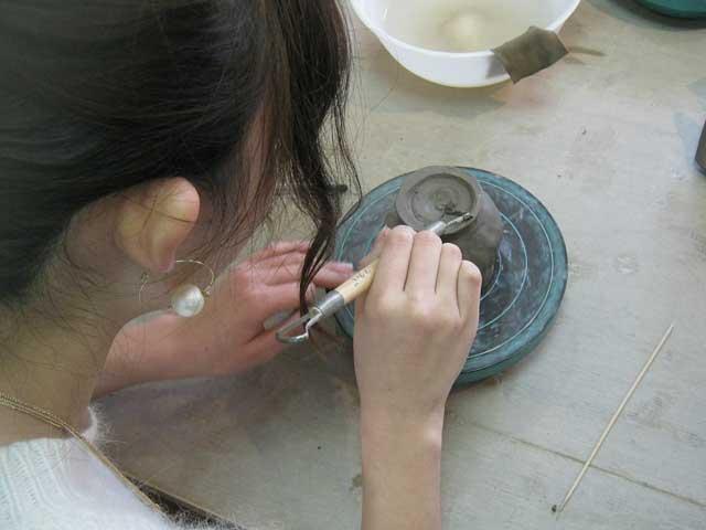 カップルの女性が高台削り工程で粘土を削っている様子