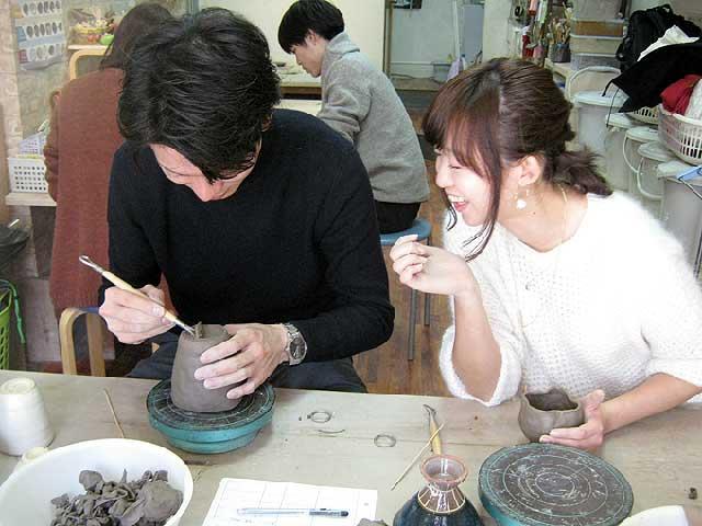 デート中のカップルが仲良く陶芸体験している姿