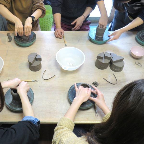 指先で陶芸粘土を加工していくお客さんたち