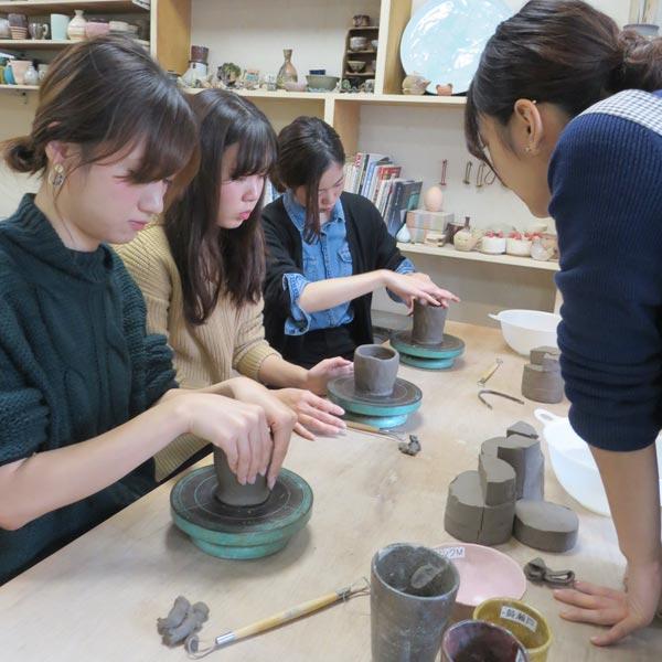 女子会の陶芸教室でお客さんを指導する女性講師