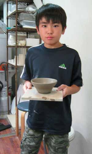 男の子が電動ろくろで作ったお茶碗を見せているところ