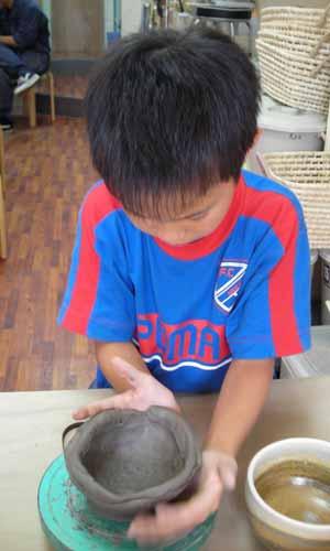男の子がお茶碗の形を修正しているところ