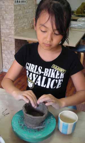 小学生の女の子が手びねりでお茶碗を作っているところ