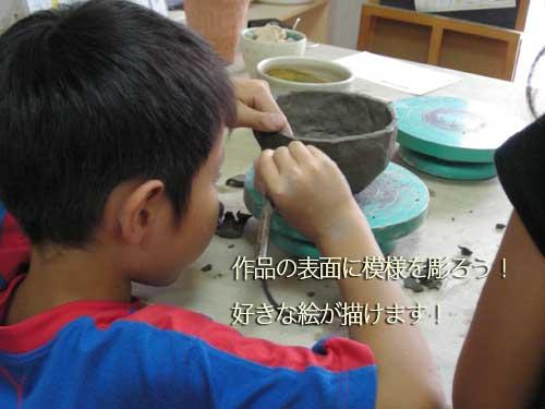 茶碗の表面の装飾を楽しんでいる少年