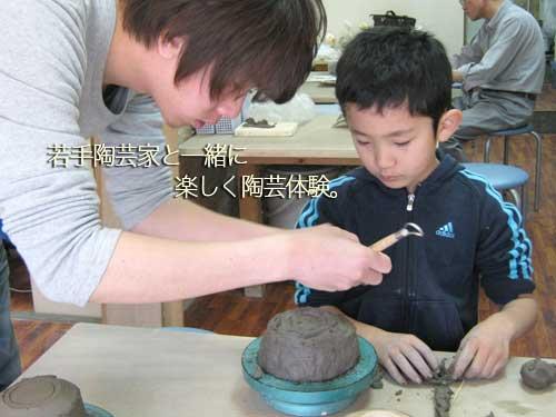 陶芸教室の先生に茶碗の作り方を教わる少年