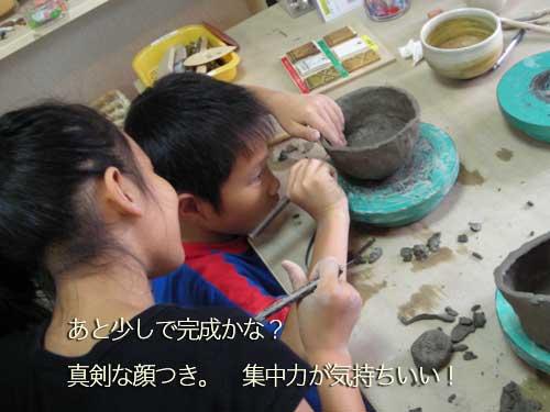 兄弟で集中して陶器を作っている様子