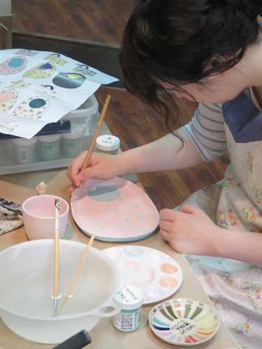 陶芸教室の会員さんが絵の具で絵を描いている