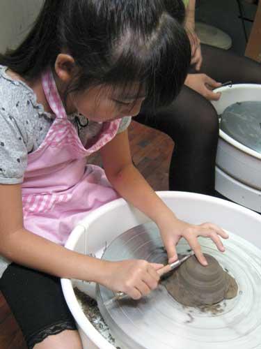 小学生の女の子が電動ろくろで陶芸体験で作っているお茶碗削り