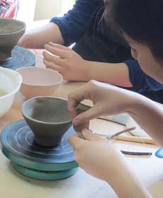 陶芸体験で口元を綺麗に仕上げている講師