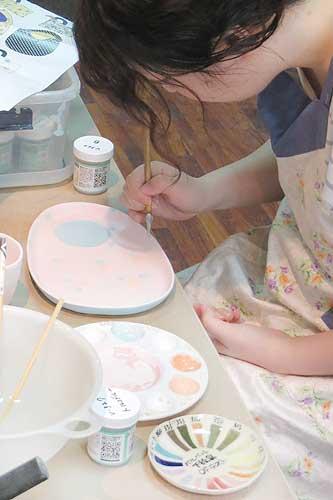 女性がお皿に花の絵付けをしている